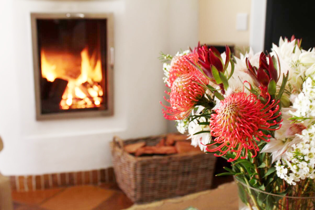 Living area with a cosy fireplace and locally grown proteas