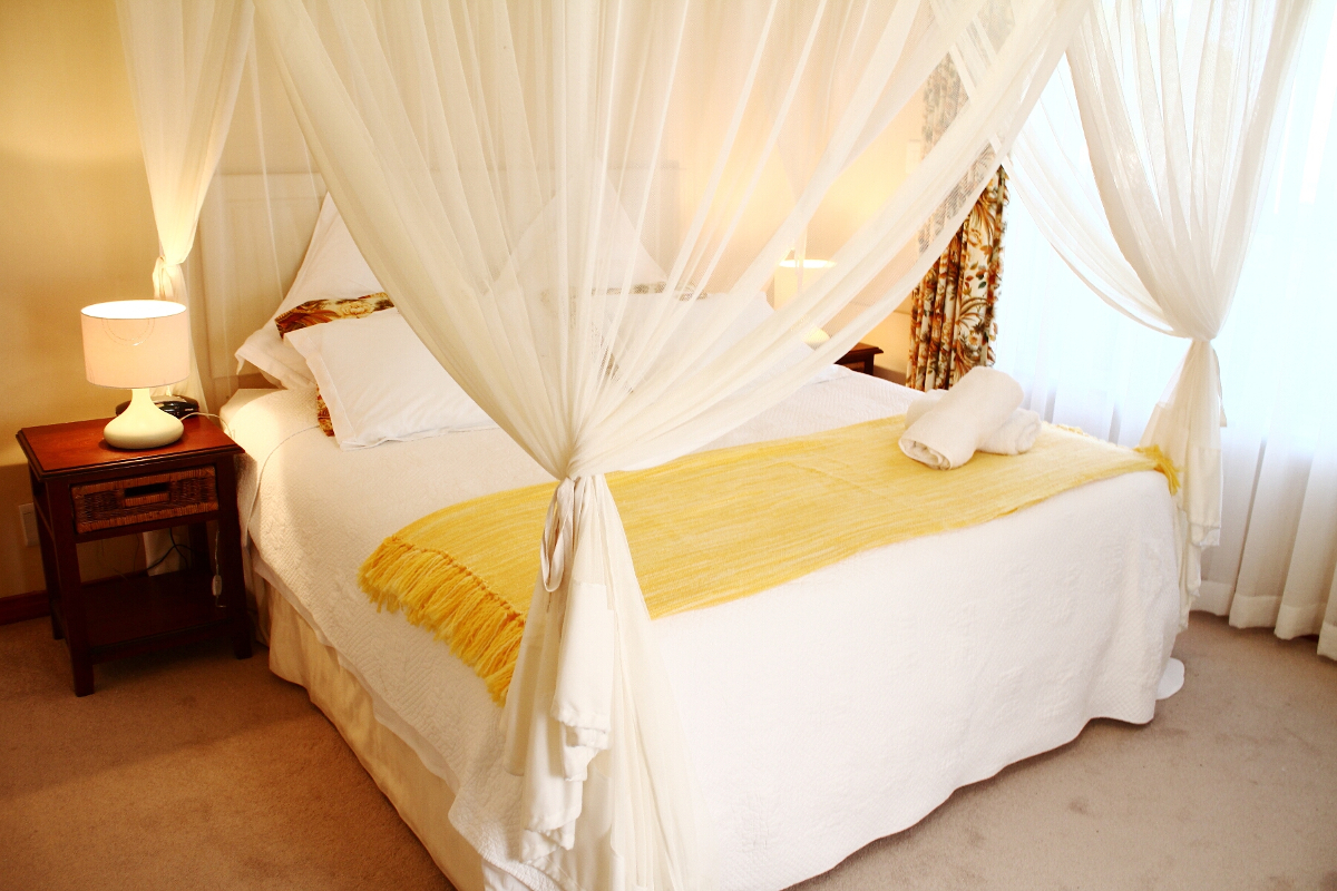 Double bed with a bedside table and mosquito netting