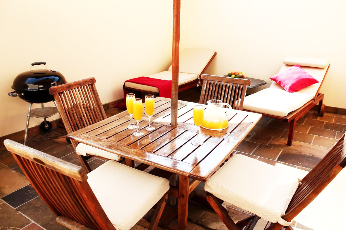 Private outside area with pool chairs, a table and fruit bowel