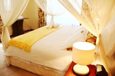 Double bed with mosquito netting and bedside lamp