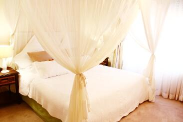 Double bed with mosquito netting and complimentary chocolates